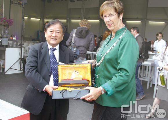 图为王晓华董事长向阿尔默勒市市长安娜玛丽·约里斯玛女士赠送礼物