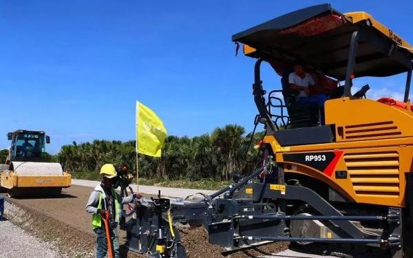 上图为徐工RP953摊铺机高端机型携手徐工单钢轮压路机助力东帝汶高速公路建设