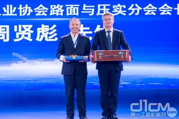 中国工程机械工业协会路面与压实分会会长周贤彪将1984年参加徐工CA25压路机下线时徐工赠送的箱子在2018年的今天捐赠给徐工,上图为双方互换礼物场景。