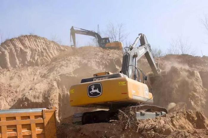 约翰迪尔挖掘机在铲平小山