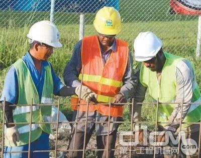 中国工人在圭亚那德莫拉拉东海岸道路升级改造项目向圭亚那工人讲解技术要领