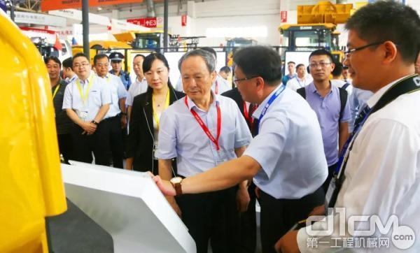 徐工集团董事长、党委书记王民在展位前了解参展产品