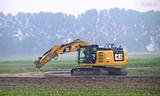卡特彼勒323E挖掘机在农田铺设水管