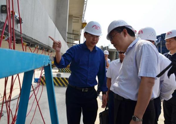 铁科院科管部部长胡所亭向周黎一行介绍机制砂试验梁的静载试验相关情况