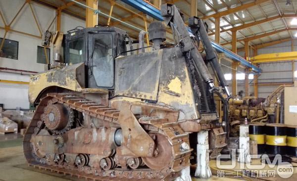 某工程机械维修企业的厂房中一台推土机等待维修
