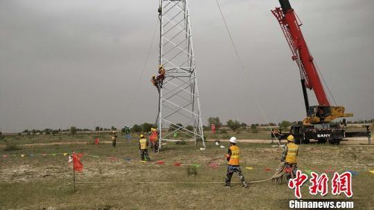 图为工人们进行铁塔组立