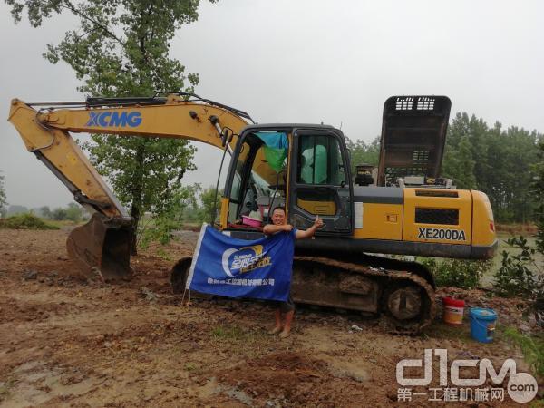 徐工挖机服务人员冒雨为刘伟的挖掘机做维护