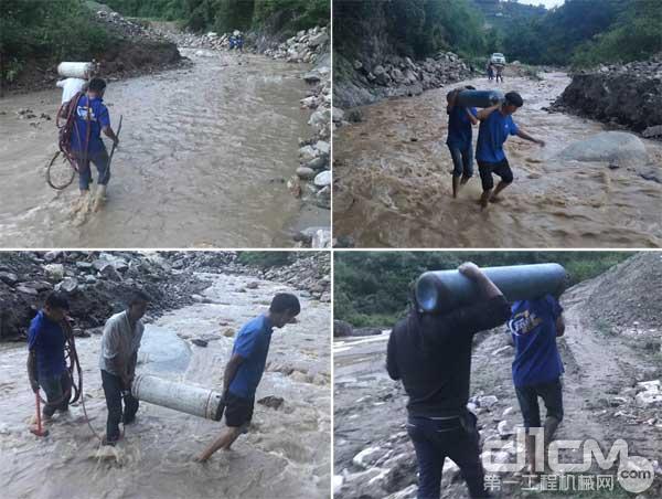 彭主管和徐工挖机服务人员人工搬运设备过河