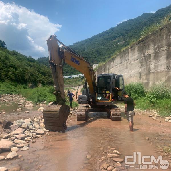 徐工挖机服务人员把挖机开到河滩边清洗设备