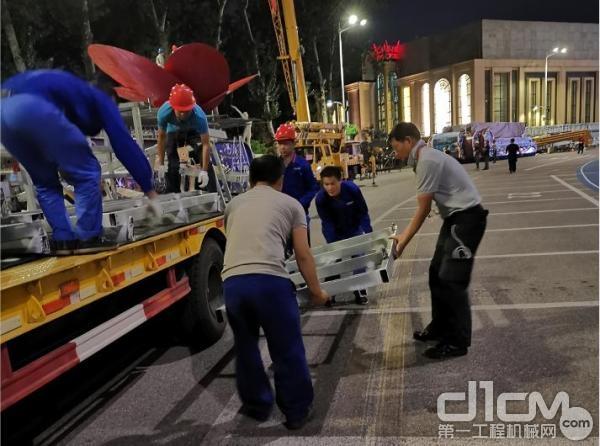 湖南彩车制作小组副组长王旭虹与组员一起搬运物料