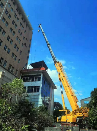 台州某地徐工XCT55L6伸出主臂四节,吊装高度25米,修复着被台风吹落的广告牌。