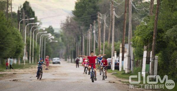 哈萨克斯坦本地儿童在新建成的公路上玩耍