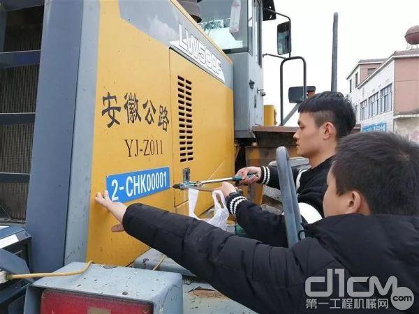 工作人员正在给车辆安装首张非道路移动机械环保号牌