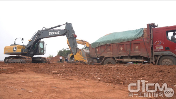 约翰迪尔E210LC挖掘机在协助工地自卸车走出陷坑