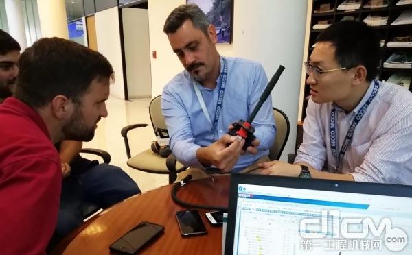 潍柴员工李篷(右一)正与同事一起为阿根廷客户讲解产品常识