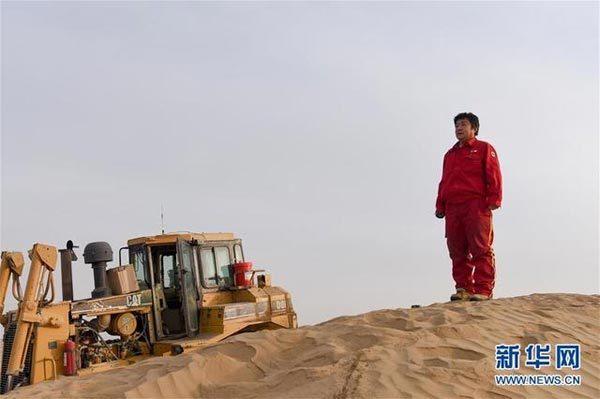 在塔克拉玛干沙漠腹地,东方物探塔里木物探处2113队的推土机手胡军爬上大沙包观察前方沙漠情况(1月13日摄)。新华社记者 丁磊 摄
