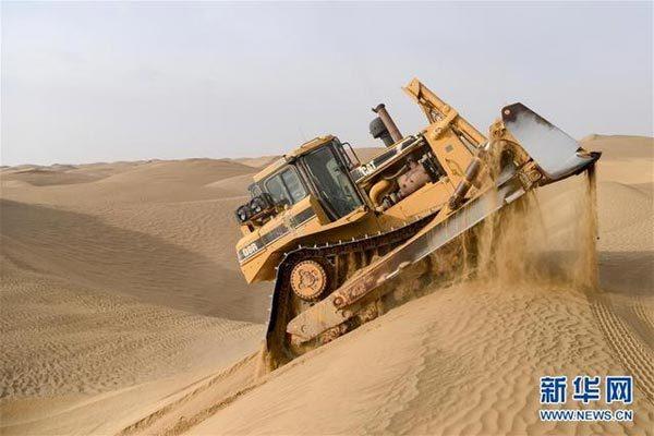 在塔克拉玛干沙漠腹地,东方物探塔里木物探处2113队的推土机手胡军驾驶推土机冲上一个大沙丘(1月13日摄)。新华社记者 丁磊 摄