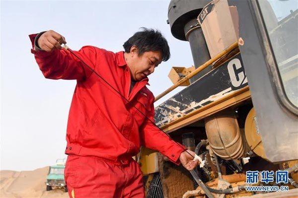 在塔克拉玛干沙漠腹地,东方物探塔里木物探处2113队的推土机手胡军在查看推土机机油情况(1月13日摄)。新华社记者 丁磊 摄