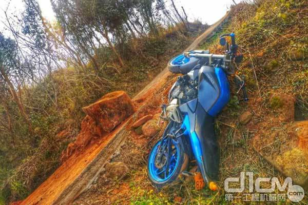同行摩友的一辆升仕牌摩托车躺在路旁
