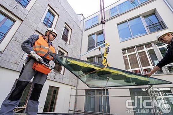 每个玻璃面板重达800公斤,并使用真空提升装置将其固定在起重机吊具上