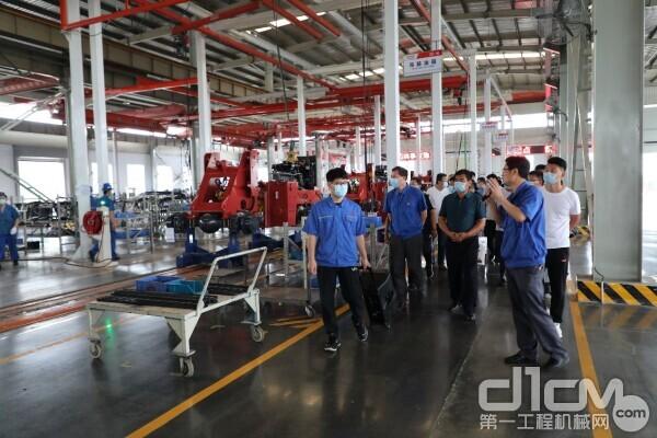 客户们来到公司总装车间,参观了装载机装配流程