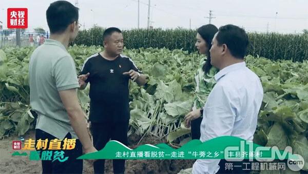 徐工大客户王迪坤向主持人热情介绍他的奋斗故事