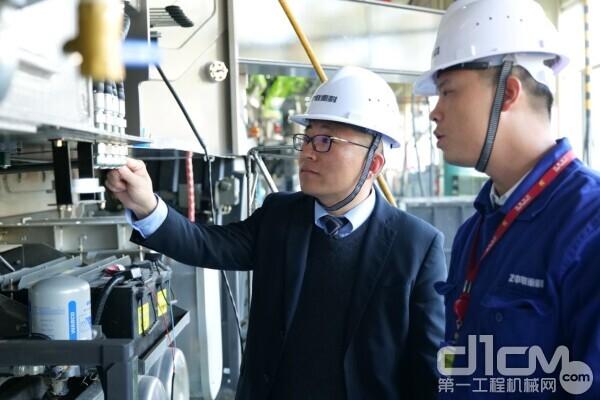 中联重科混凝土泵送机械分公司研发中心经理高荣芝(左一)在车间研究泵车装备