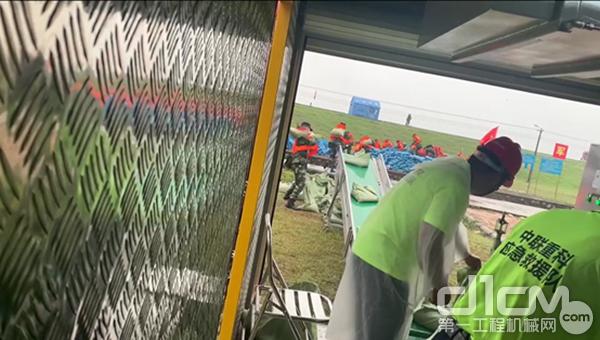 △中联重科救援队员在应急砂石打包模块车中操作