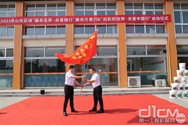 图片英轩重工总经理助理、装载机事业部总经理王军为昌乐携创贸易张总授予走访旗帜