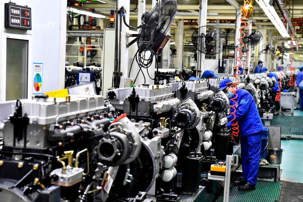 4月22日,在位于山东潍坊的潍柴集团总装车间,工人在流水线上装配发动机(新华社记者郭绪雷摄)